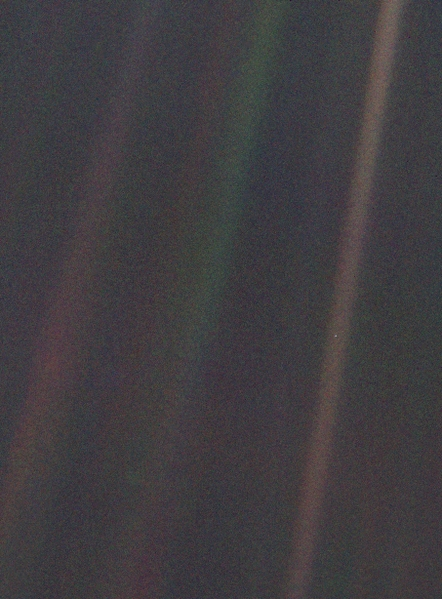 Seen from about 6 billion kilometers (3.7 billion miles), Earth appears as a tiny dot (the blueish-white speck approximately halfway down the brown band to the right) within the darkness of deep space